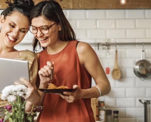 Deux jeunes femmes amies sont dans une cuisine. Elles rient ensemble et regardent un ipad. L'une des amies mange des pâtes.