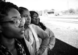 3 femmes noires se tiennent debout côte à côte et regardent de façon inspirée à l'horizon