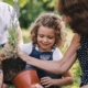 Une petite fille jardine avec ses grand-parents dans la cour. La grand-mère sort une plante de lavande d'un pot pour la transplanter. Tout le monde sourit gaiement.