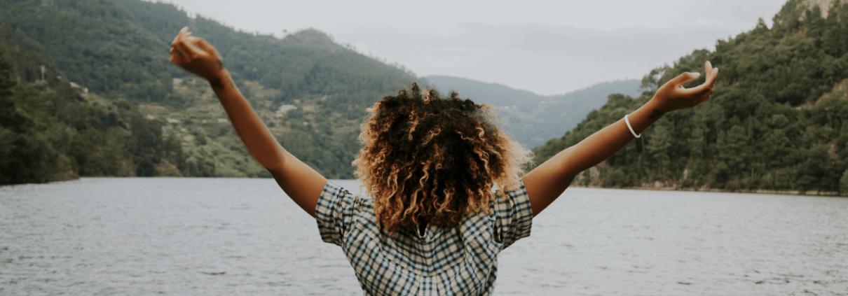 Une jeune femme noire pose de dos les bras en l'air. Elle est sur le bord d'un lac et a une posture inspirée et confiante.