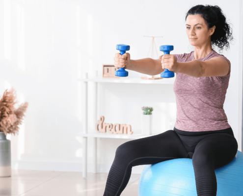 Une femme fait un cours d'exercice à la maison. Elle est assise sur un ballon suisse en levant des poids et haltères