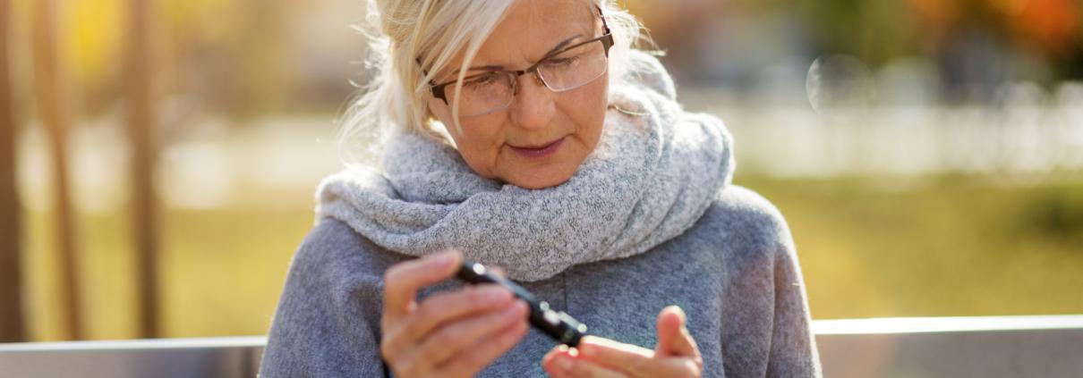 Une femme aînée vérifie son taux de glycémie sur un banc de parc à l'extérieur.