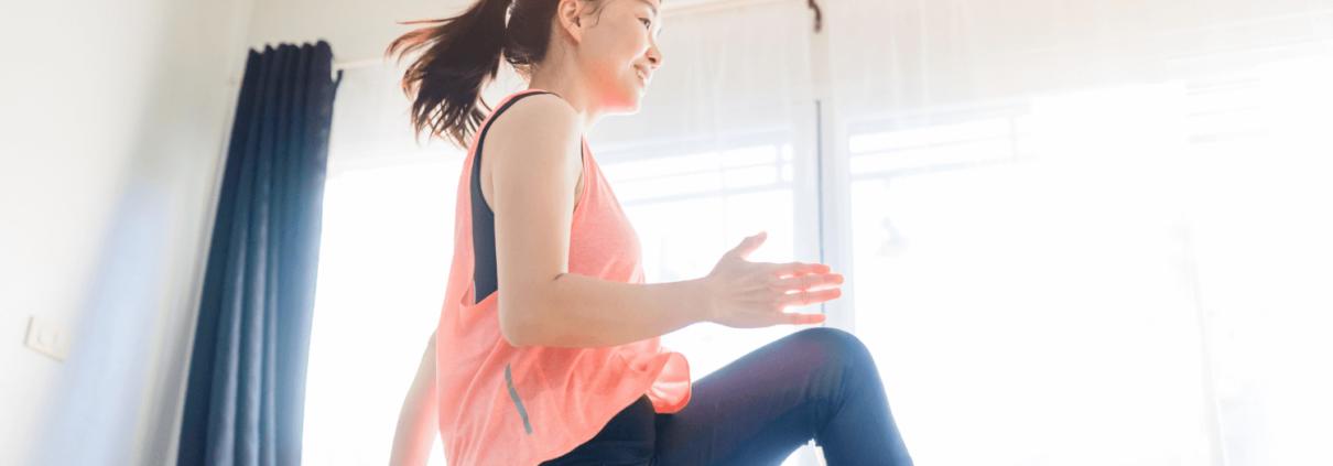 Une jeune femme fait un cours d'activité physique dans son salon