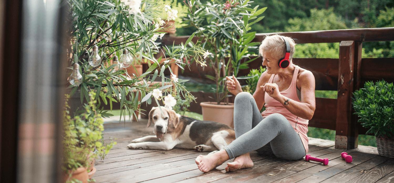 Une femme active d'âge mure est assise sur son balcon avec son chien en écoutant de la musique. Elle s'apprête à faire un entraînement physique avec des petits poids et haltères. C'est l'été et son balcon est rempli de belles plantes.