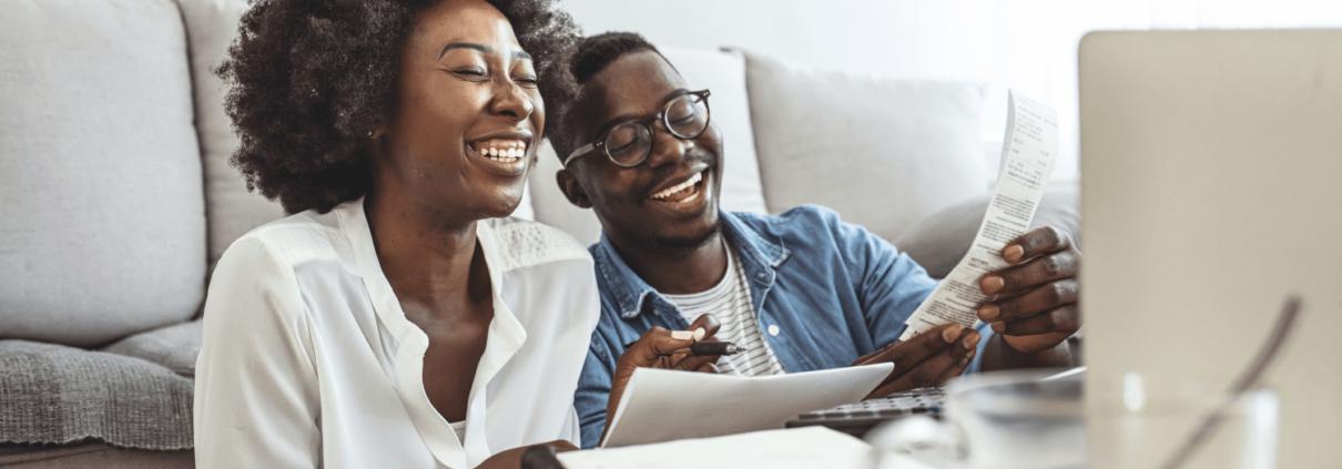 Un couple rient ensemble dans leur salon. Ils tiennent des papiers et sont devant un portable - ils travaillent sur leurs finances.