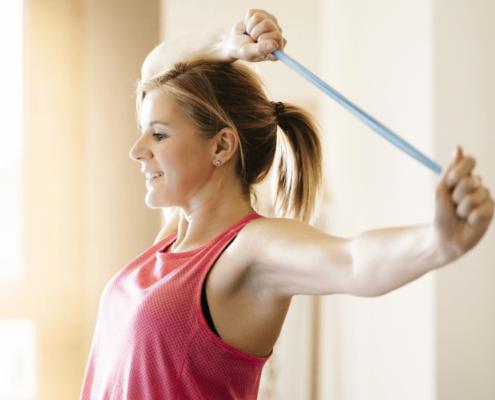 Une jeune femme fait des exercices avec un élastique